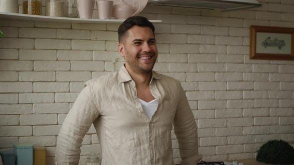 Thumbnail for Ein gutaussehender Mann auf dem Hintergrund der Küche mit jemandem reden und Blick auf die Kamera