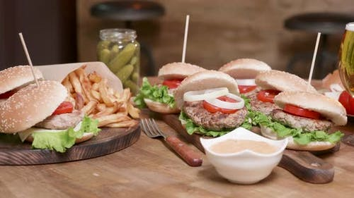 Smooth Parallax Shot of Wide Selection of Burgers on a Wooden Round Table