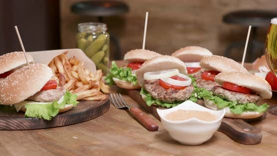 Thumbnail for Smooth Parallax Shot of Wide Selection of Burgers on a Wooden Round Table