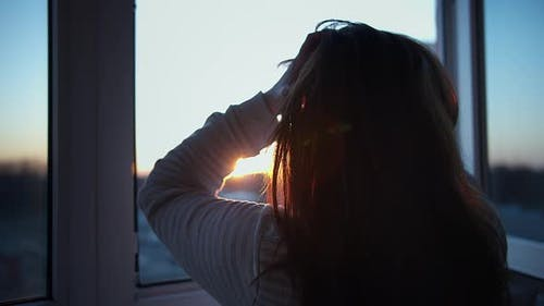 Woman Stands on the Balcony at Sunset and Looks Out the Window, Touches Her Hair