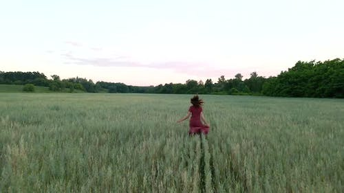 Young Woman with Long Hair in Long Dress Runs on a Field, Slow Motion  Shot