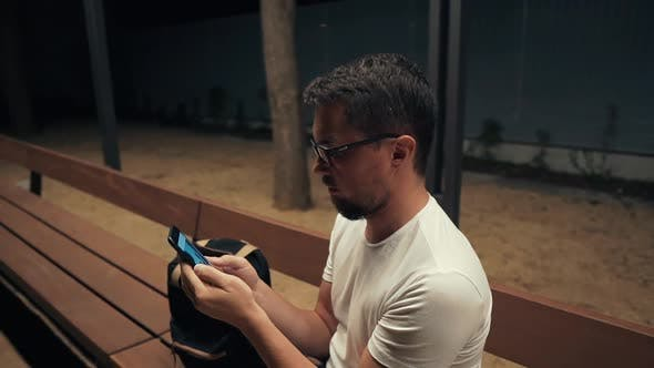 Thumbnail for Adult Man Is Watching Pictures in Mobile Phone, Sits Alone in Evening Outdoors