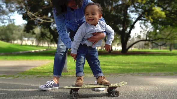 Young Mixed-race Mother Holding Her Son on Skateboard in Park