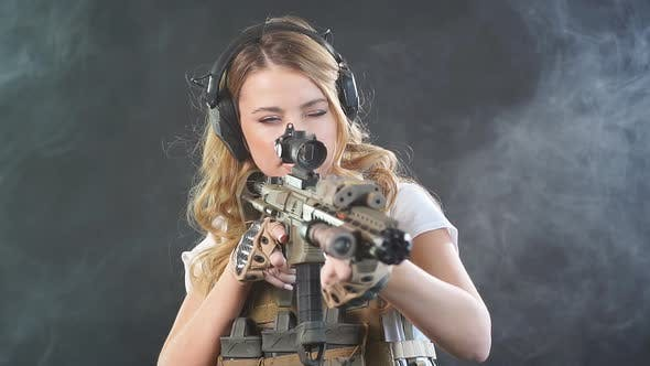 Airsoft Female Shooter Holding an Automatic Assault Rifle and Aiming at Enemy. Slow Motion