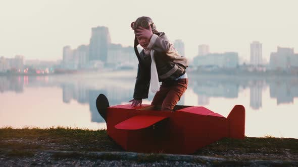 Thumbnail for Little Happy Pilot Boy Getting Into Fun Red Cardboard Plane Costume at Amazing Peaceful City Lake