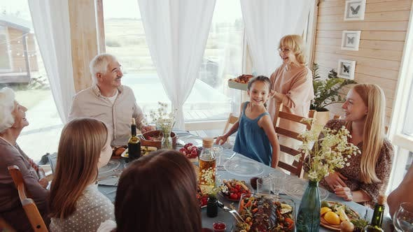 Thumbnail for Happy Grandmother Serving Holiday Dinner for Large Family