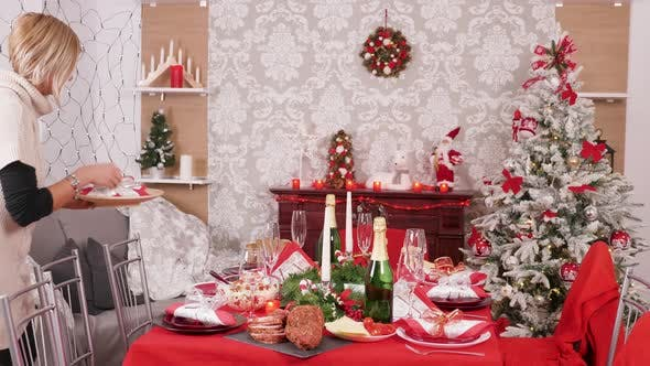 Cover Image for Young Beautiful Woman Preparing Dinner Table for Christmas Celebration