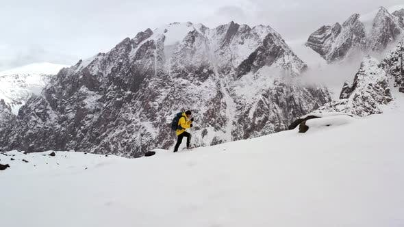 Thumbnail for Young Man Yellow Jacket Walking Up Mountain Slope Backpacking Winter Hike Extreme Conditions Swiss