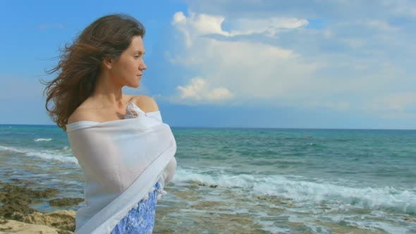 Thumbnail for Lonely Brunette Wrapping Herself in Scarf, Looking at Ocean Waves. Windy Weather