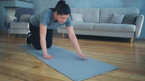 Sportive Woman Does Plank Exercise in Room
