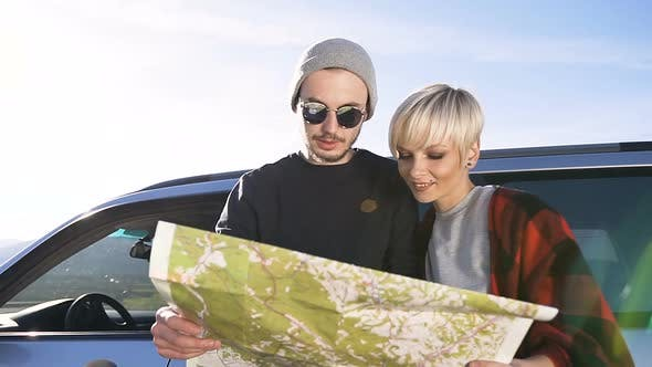 Couple of Traveler in Love Standing in front of Car and Considering the New Routes a Map
