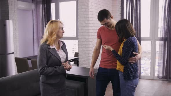Thumbnail for Senior Estate Agent Giving Home Keys To Couple