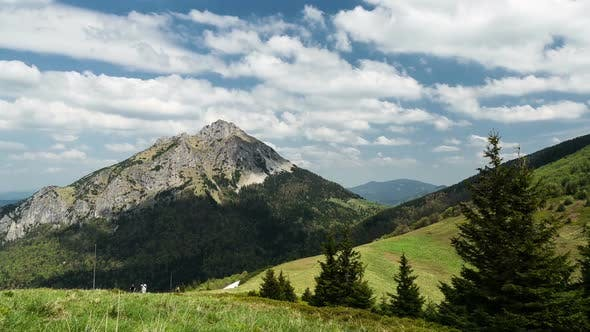 Thumbnail for Fast Moving Clouds and Shadows over Peak and Trees in Mountains