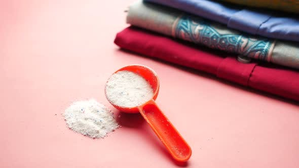 Washing Powder in Plastic Spoon on Blue Background