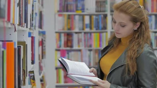 Portrait of a Young Beautiful Woman with Bright Red Hair in Glasses, Pretty Girl Reading in Book