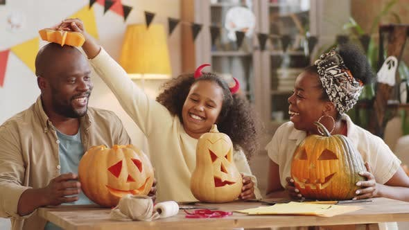 Thumbnail for Joyous Black Family Playing with Carved Pumpkins on Halloween