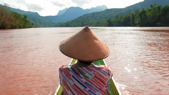 Thumbnail for Woman with traditional hat cruising on the brown water of river in Laos