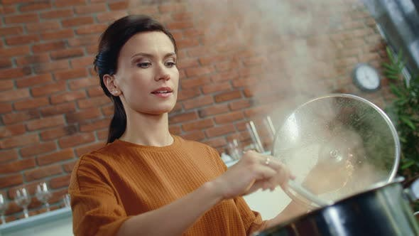 Thumbnail for Elegant Woman Stirring Soup with Spoon. Young Girl Smell Food From Boiling Pot