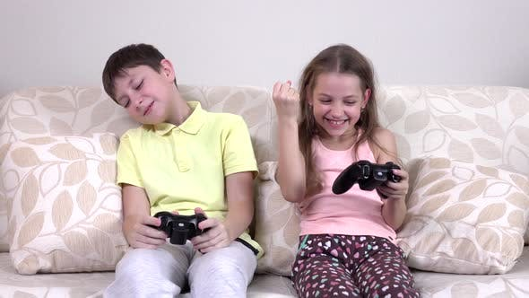 Thumbnail for Brother and Sister Playing Video Games Lying on the Couch