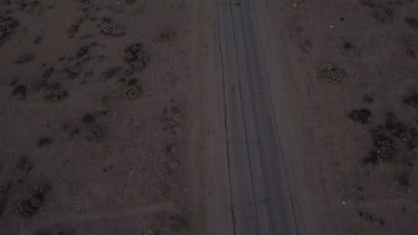Cover Image for AERIAL: Birds View of Lonely Abandoned Desert Road with Red Car Driving in the Distance