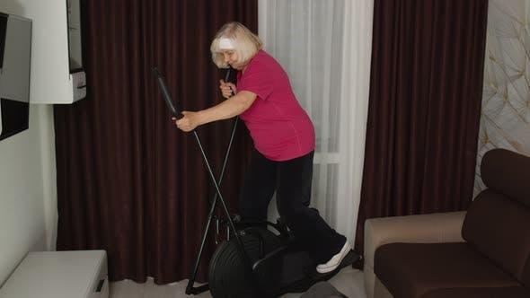 Thumbnail for Senior Mature Grandfather and Grandmother Using Orbitrek Doing Weight Lifting Dumbbells Exercises