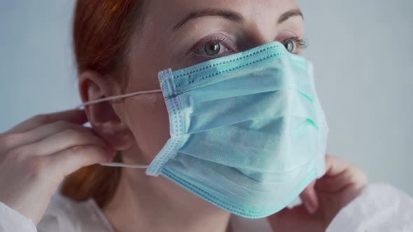 The Nurse Puts on a Protective Mask.