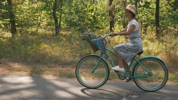 Thumbnail for Happy woman rides vintage bicycle with flowers in basket, enjoying sunny day in park.