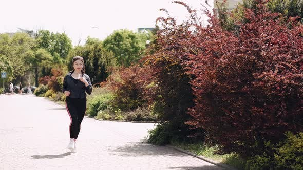 Pretty Athletic Woman Is Jogging Outdoors
