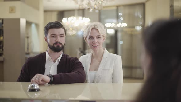 Portrait of Confident Adult Caucasian Couple Talking with Receptionist in Hotel