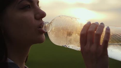 Woman Quenches Her Thirst in a Field at Sunset