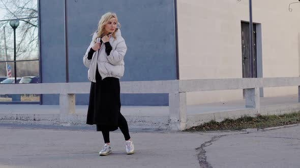 Thumbnail for Outdoor Shot of a Blonde Model Posing in a Trendy Grey Coat By the Building in Autumn