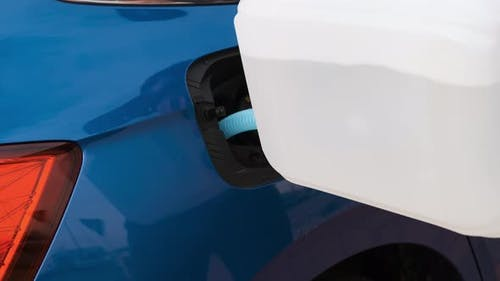 Close Up Man Filling a Diesel Engine Fluid From Canister Into the Tank of a Blue Car