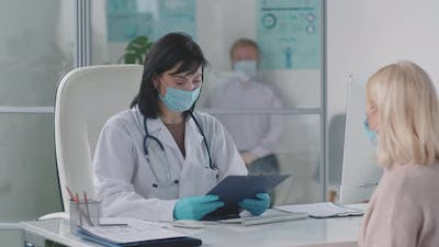 Female Doctor in Mask Giving Healthcare Consultation to Woman
