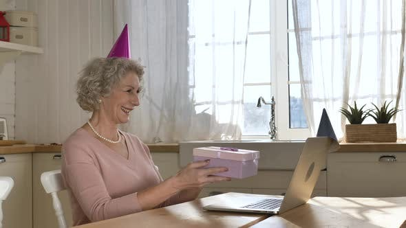 Grandmother Enjoys Online Birthday Holding Present Box