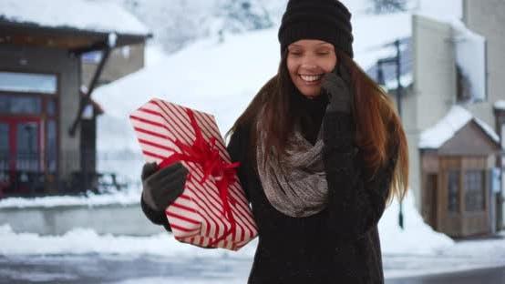 Thumbnail for Frau auf Handy während halten Weihnachtsgeschenk auf verschneite Straße Innenstadt