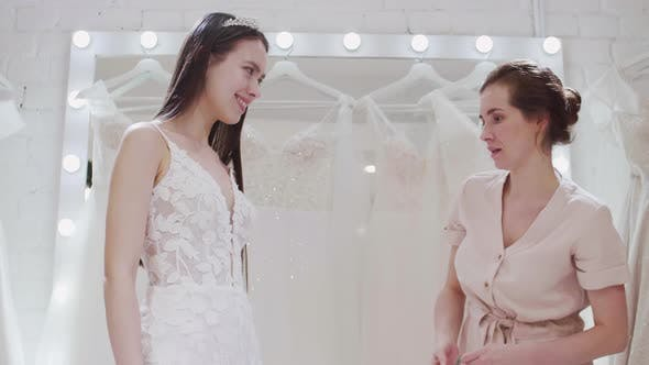 Thumbnail for Saleswoman Making Measurements of Bride Figure