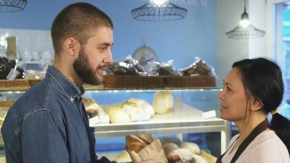 Cover Image for Handsome Young Man Buying Fresh Bread From a Female Baker