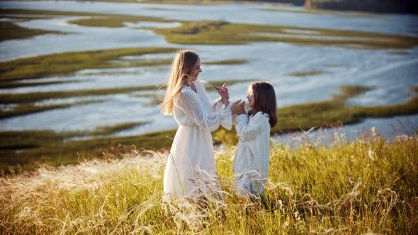 Thumbnail for Happy Family Concept - Little Girl and Her Mother Hugging on the Wheat Field