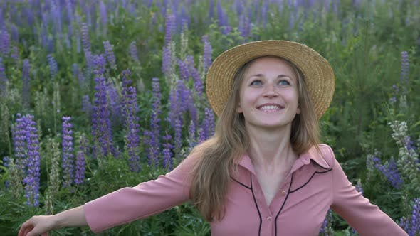 Thumbnail for Mädchen in rosa Kleid und Strohhut dreht sich um in Lupin Feld