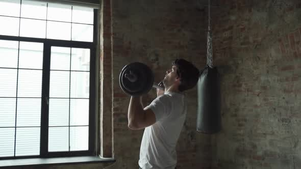 Muscular Fitness Man Lifting Barbell Above His Head in Modern Gym