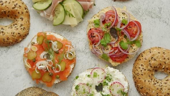 Hausgemachte Bagel Sandwiches mit verschiedenen Belägen, Lachs, Hüttenkäse, Hummus, Schinken, Rettich