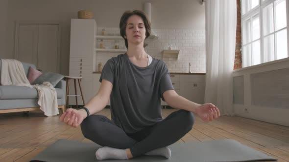 Young Woman Meditates at Home