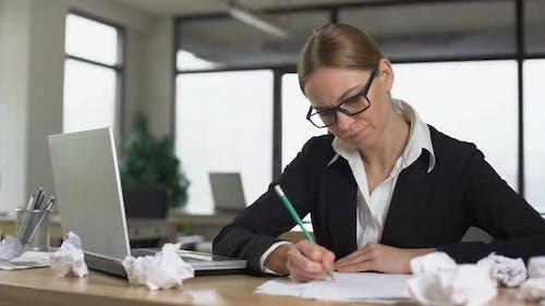Jeune femme d'affaires manque d'idées pour démarrer et froisser les papiers, non motivé