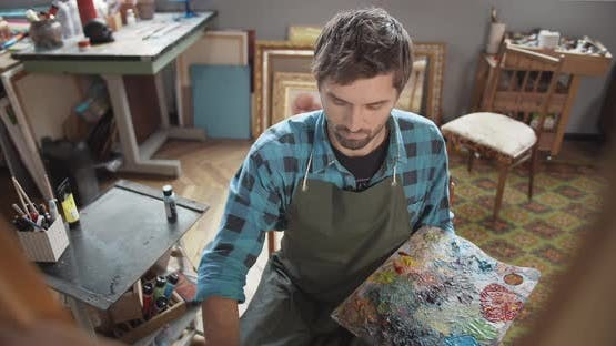 Male Painting on Molbert in Studio