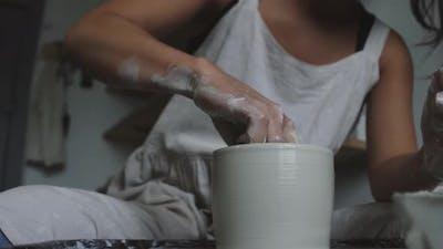 Female potter molding wet clay pot with wet sponge