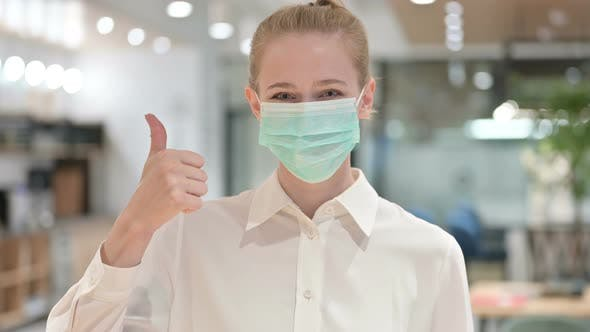 Cover Image for Portrait of Young Businesswoman with Face Mask Showing Thumbs Up