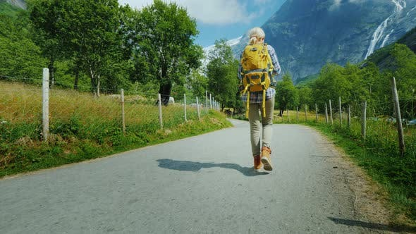 Thumbnail for The Incredibly Beautiful Nature of Norway - a Woman with a Backpack Walking Along a Path