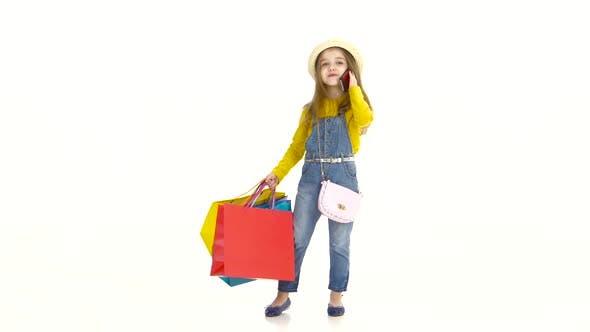 Thumbnail for Little Girl Holding Bags and Talking on the Phone, Smiling. White Background