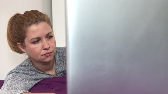 Thumbnail for Caucasian woman on mobile computer relaxed in bed  4K 2160p 30fps UltraHD footage - Blond female wor