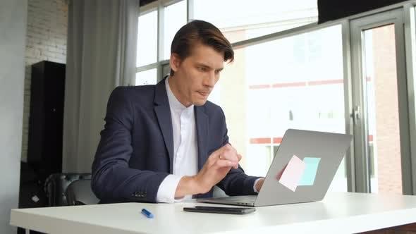 Man With Laptop Finishing Work At Office. Panning shot of businessman finishing working on laptop